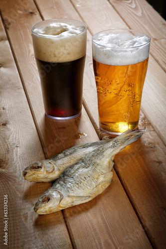 Two glasses of beer with dried fish on a table