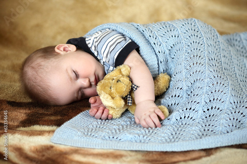 baby sleeping sweet sleep on a beige blanket