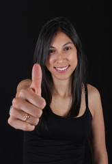 Sexy woman with thumbs up black background