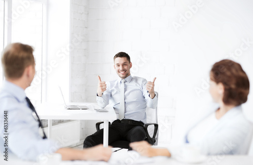 businessman showing thumbs up in office