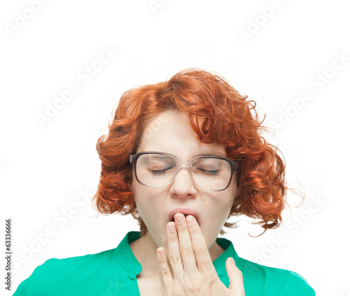 red-haired girl in glasses yawning on white background