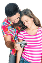 Hispanic father and his daughter looking at images on a camera