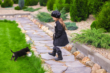 Adorable little girl playing with small puppy in the garden