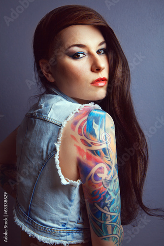 Beautiful girl with stylish make-up and tattooed arms.,