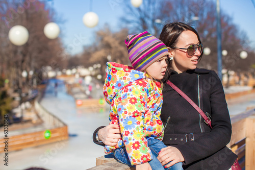 Little cute girl with her mother on sunny day outdoors