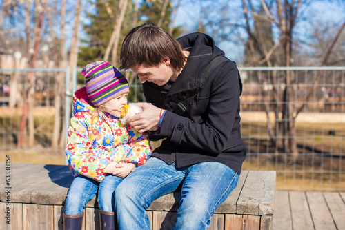 Little adorable girl and father eating corn in the park on a
