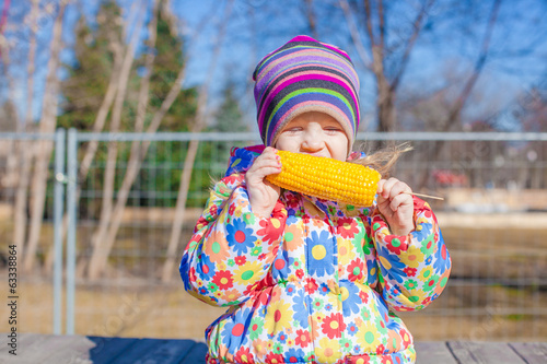 Little adorable girl eating corn in the park on a warm spring