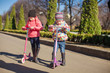 Two little sisters ride scooters on a warm sunny spring day