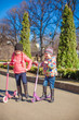 Little adorable girls with scooter in spring park at warm day