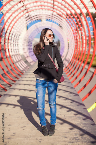 Young buzy happy woman talking on the phone outdoors