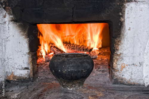 Old russian stove with iron pot a burning firewood