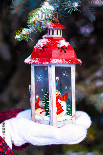 Beautiful red vintage Christmas lantern on warm mittens