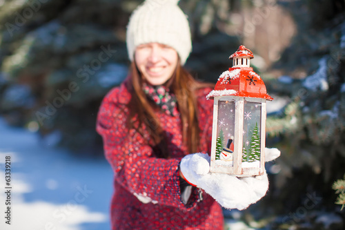 Young beautiful happy woman with red Christmas lantern in the