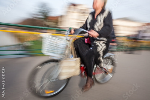 Old woman riding a bicycle around the city