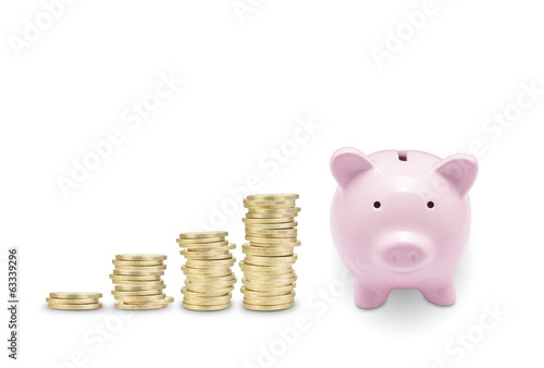 Pink piggy bank and coins. Isolated on white