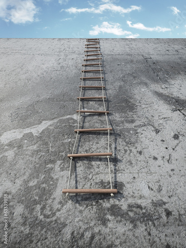 Rope-ladder on grunge wall in front of sky