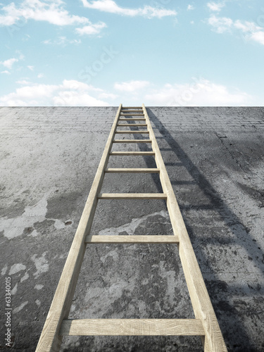 Ladder on grunge wall in front of sky