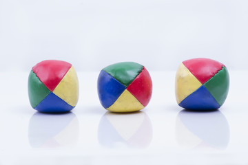 Juggling balls in a row (studio white background)