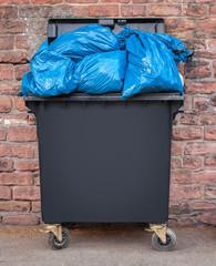 Restmülltonne mit blauen Müllsäcken