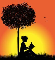 donna silhouette che legge un libro sotto un albero
