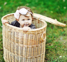 Sweet little girl looks out of a basket in a summer park