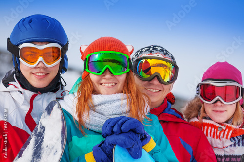 Four happy snowboarders wearing goggles