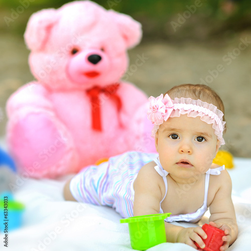 Sweet baby girl with teddybear the background outdoors