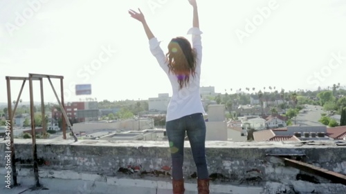 Woman on a rooftop with her arms wide open looking at view
