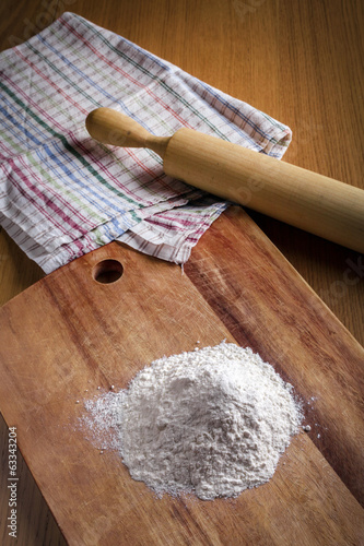 Flour, rolling pin and a towel on the table
