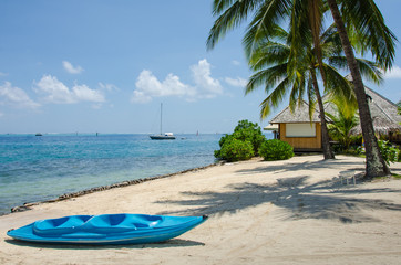 Blue kayak on beach on a tropical island