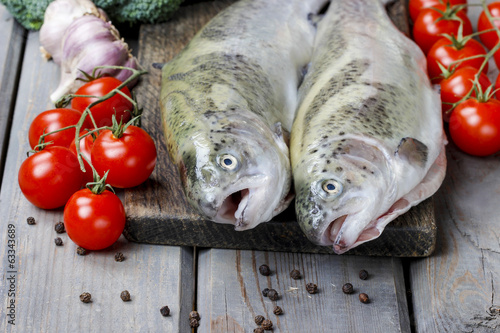 Two rainbow trouts, tomatoes and garlic on rustic wooden table