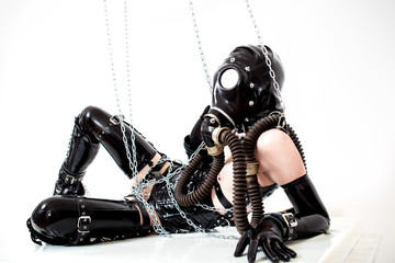 Woman chained on the floor with a gas mask
