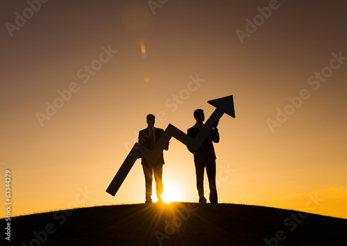 Businessmen holding the increase graph on the hill