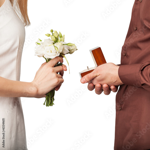Wedding couple holding ring box and a bouquet of flowers