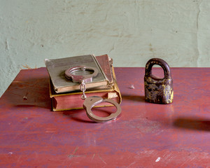 Objects from a jail set on a desk including handcuffs