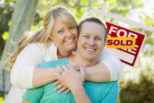 Happy Couple In Front Sold Real Estate Sign