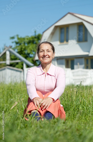 Happy mature woman sitting against home