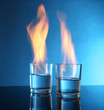 Glasses with burning alcohol on blue background