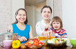 woman and adult daughter with girl cooking salad