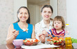 women with child together eats veggie lunch