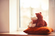 Two embracing living teddy bear toys sitting on window-sill - 63347624