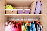Colorful clothes hanging in wardrobe