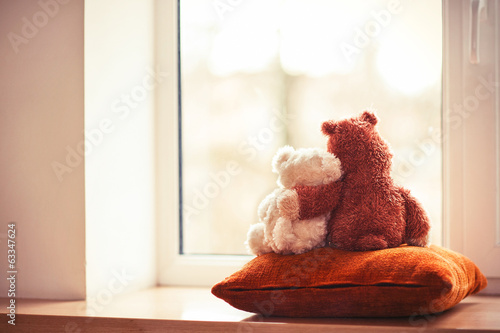 Two embracing living teddy bear toys sitting on window-sill