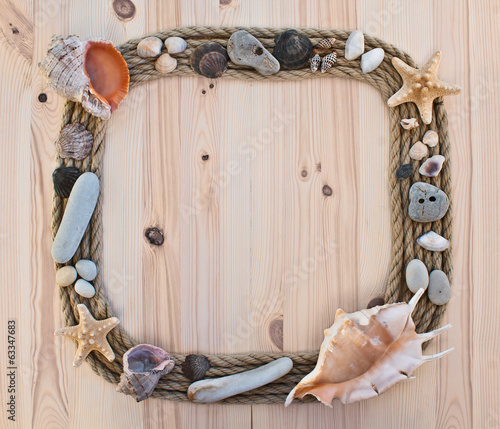 frame of rope and seashells on wooden background