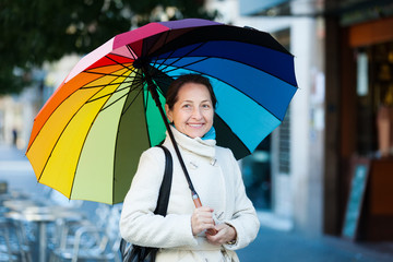 mature woman with umbrella in autumn