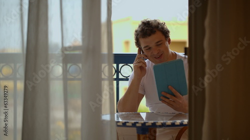 Man busy with phone talk and touchpad