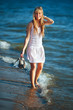 pretty woman in a white dress on the ocean coast