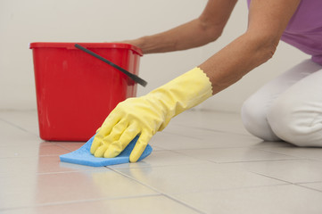 Cleaning floor tiles with sponge and glove.