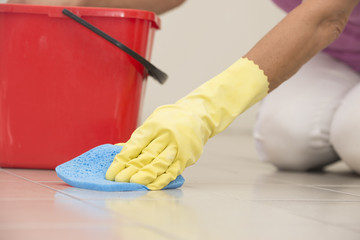 Cleaning floor tiles with glove and sponge