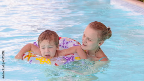 Mother and son swimming in the pool